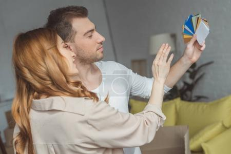side view of young couple looking at palette and choosing color while renovating apartment