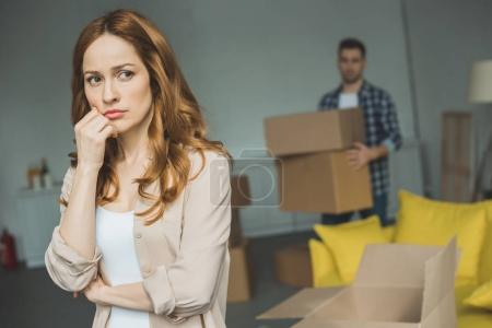 Photo for Serious young woman standing with hand on chin while husband holding cardboard boxes behind during relocation - Royalty Free Image