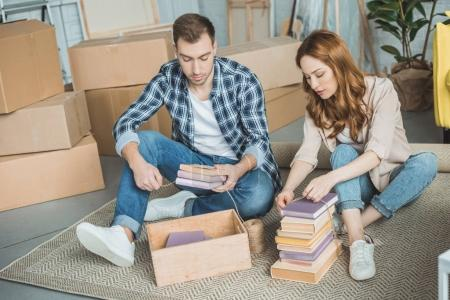 Photo for Young couple sitting on carpet and packing books in box during relocation - Royalty Free Image