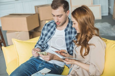young couple taking notes and counting money while moving home