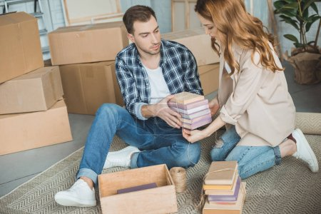 Photo for Young couple packing books in cardboard box while moving home - Royalty Free Image