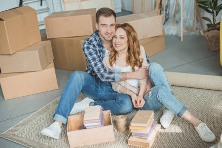Photo for Happy young couple sitting together and smiling at camera while packing boxes during relocation - Royalty Free Image