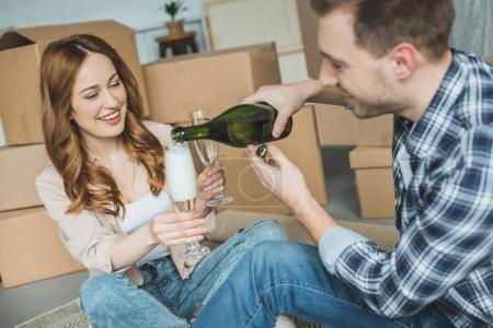 happy young couple celebrating relocation with champagne in new home