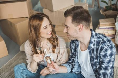 couple holding glasses of champagne and smiling each other while celebrating relocation