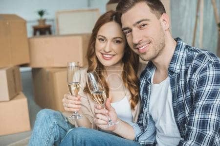 Photo for Happy young couple couple holding glasses of champagne and smiling at camera while celebrating relocation - Royalty Free Image