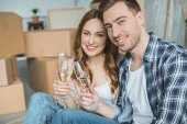 happy young couple couple holding glasses of champagne and smiling at camera while celebrating relocation