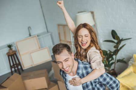 happy couple piggybacking at new apartment with cardboard boxes, relocation concept