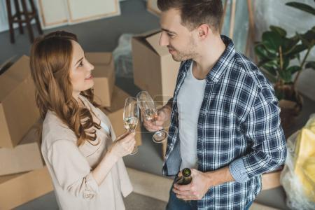 Photo for High angle view of smiling couple drinking champagne at new apartment, relocation concept - Royalty Free Image