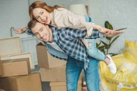 Photo for Happy couple piggybacking at new apartment with cardboard boxes, relocation concept - Royalty Free Image