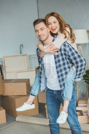 smiling couple piggybacking at new apartment with cardboard boxes, relocation concept