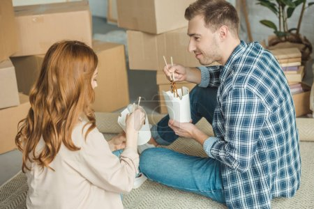couple eating asian food at new apartment with cardboard boxes, moving home concept