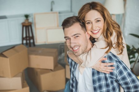 Photo for Portrait of happy wife hugging husband at new home with cardboard boxes, relocation concept - Royalty Free Image