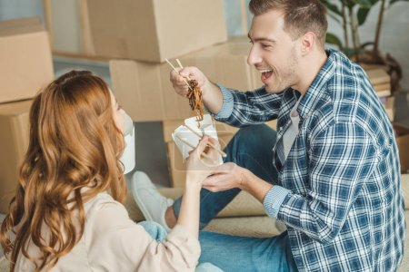 Photo for Couple eating asian food at new apartment with cardboard boxes, moving home concept - Royalty Free Image