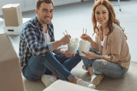 Photo for Smiling couple eating asian food at new apartment, moving home concept - Royalty Free Image