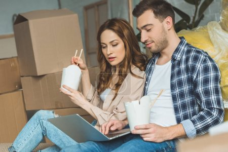 Photo for Couple eating asian food while using laptop at new apartment, moving home concept - Royalty Free Image