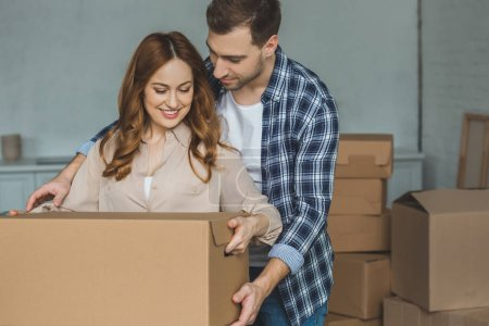 Photo for Portrait of smiling couple with cardboard box at new home, moving house concept - Royalty Free Image