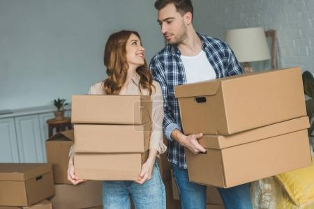 Photo for Portrait of young couple with cardboard boxes looking at each other at new home, moving house concept - Royalty Free Image