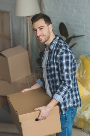 Photo for Smiling man with cardboard box in hands at new home, relocation concept - Royalty Free Image