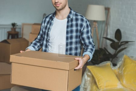 Photo for Partial view of man with cardboard box in hands at new home, relocation concept - Royalty Free Image