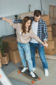 young couple having fun with skateboard at new apartment with cardboard boxes, relocation concept