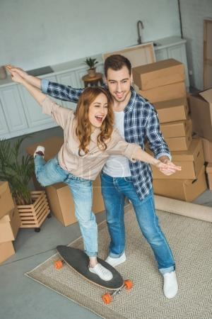 Photo pour Jeune couple s'amuser avec la planche à roulettes au nouvel appartement avec des boîtes en carton, concept de relocalisation - image libre de droit