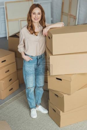 attractive smiling woman leaning on cardboard boxes at new apartment, relocation concept
