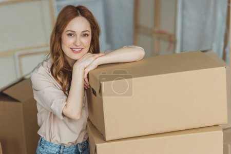 Photo for Attractive smiling woman leaning on cardboard boxes at new apartment, relocation concept - Royalty Free Image