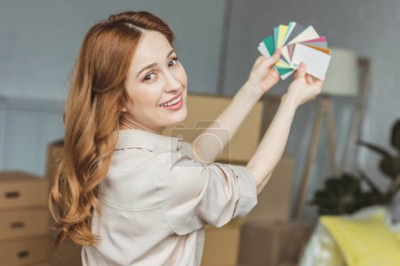 smiling woman with colors pallet for room at new home, relocation concept