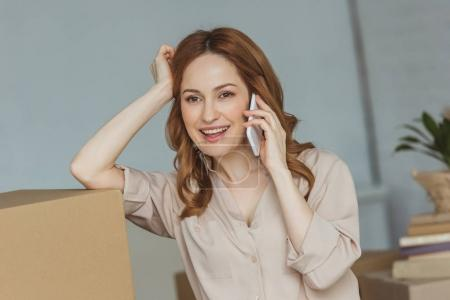 Photo for Smiling woman talking on smartphone at new apartment, relocation concept - Royalty Free Image