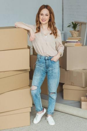 Photo for Smiling woman leaning on pile of cardboard boxes at new home, relocation concept - Royalty Free Image