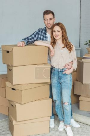 smiling couple leaning on pile of cardboard boxes at new home, relocation concept