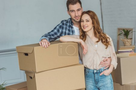 Photo for Smiling couple leaning on pile of cardboard boxes at new home, relocation concept - Royalty Free Image