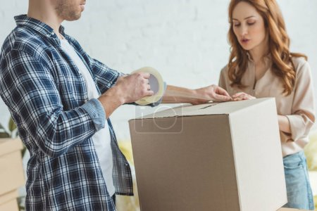 partial view of couple packing cardboard box with sticky tape together, relocation concept
