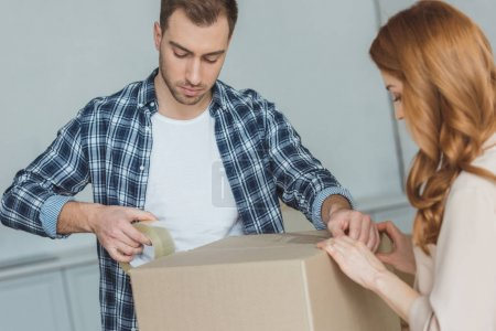 Photo for Couple packing cardboard box with sticky tape together, relocation concept - Royalty Free Image