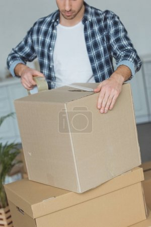 partial view of man packing cardboard box with sticky tape, relocation concept