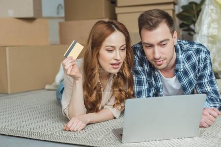 couple buying goods online together at new home, moving house concept