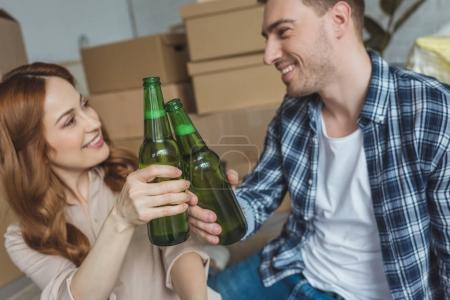 young couple clinking bottles of beer at new apartment, relocation concept