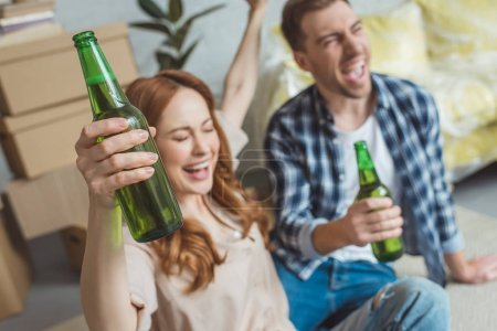 Photo for Young happy couple with bottles of beer at new apartment, relocation concept - Royalty Free Image