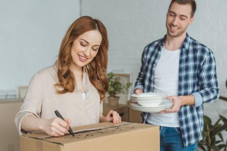 smiling woman signing cardboard box with husband with dishes near by, moving home concept