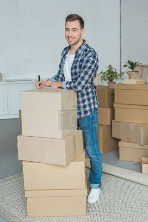 Photo for Smiling man signing cardboard box for moving home, relocation concept - Royalty Free Image