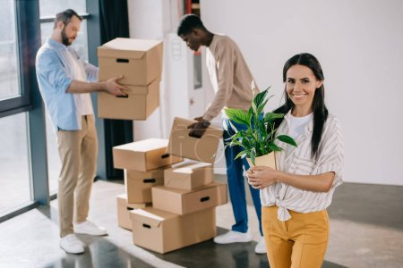Photo for Young woman holding potted plant and smiling at camera while male colleagues holding boxes behind during relocation - Royalty Free Image