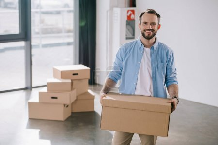 happy bearded businessman holding cardboard box and smiling at camera while moving in new office