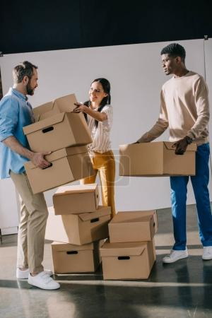 young multiethnic people holding cardboard boxes during relocation
