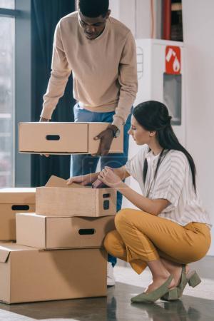 Foto de Compañeros de trabajo multiétnicos joven desembalar cajas de cartón durante la relocalización en nueva oficina - Imagen libre de derechos