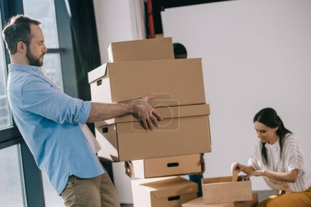 side view of bearded businessman carrying cardboard boxes in new office