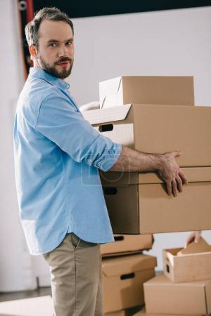 bearded businessman holding cardboard boxes and looking at camera while moving in new office