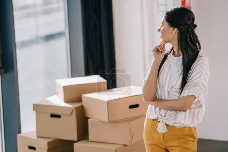pensive young woman standing with hand on chin and looking at cardboard boxes in new office