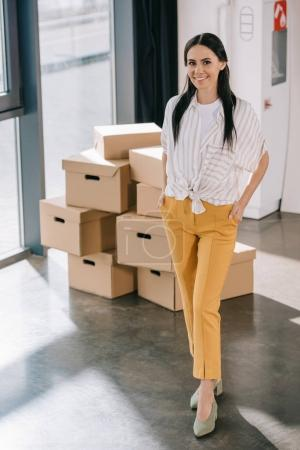 happy young businesswoman standing with hands in pockets and smiling at camera while relocating in new office
