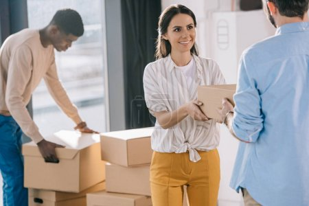 multiethnic coworkers carrying cardboard boxes during relocation in new office