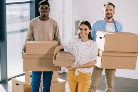 Photo for Young multiethnic coworkers holding cardboard boxes and smiling at camera during relocation - Royalty Free Image